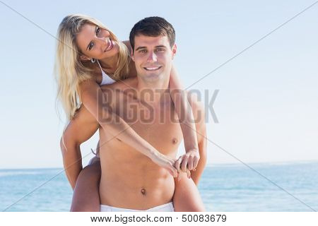 Happy man giving his pretty girlfriend a piggy back smiling at camera at the beach
