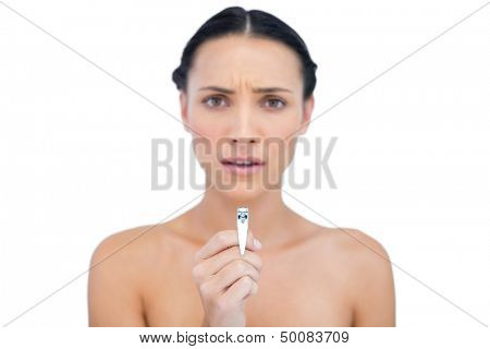 Frowning young brunette holding nail clippers on white background