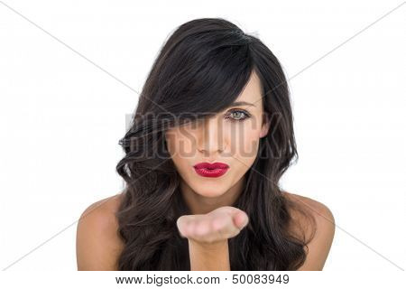 Sexy brunette with red lips blowing kiss to camera on white background