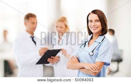 healthcare and medical concept - young female doctor with colleagues in hospital