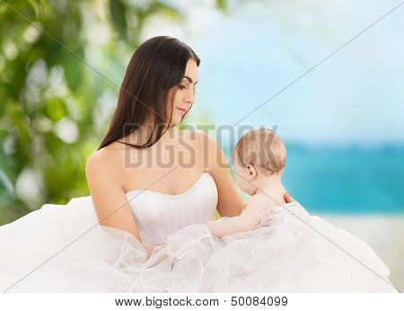 family, parenting and child care concept - happy mother in bridal dress with adorable baby
