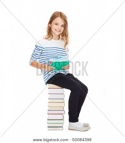 education and school concept - little student girl sitting on stack of books