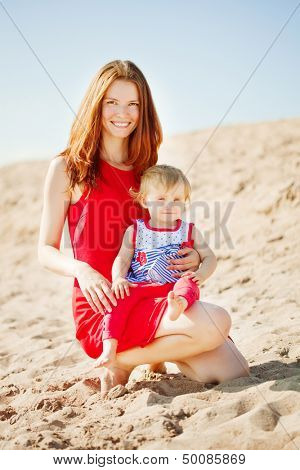 Beautiful Mom and baby outdoors. Happy family playing on the beach. Mom and baby.  Mother and child.