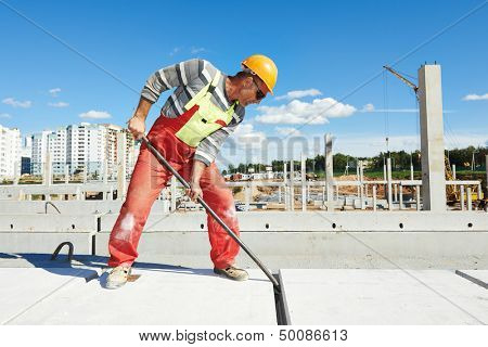 builder worker with metal crow bar installing concrete floor slab panel at building construction site