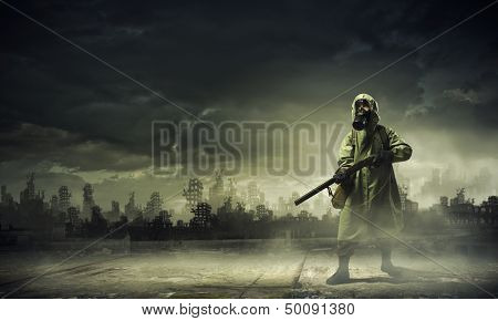 Man in gas mask and camouflage holding gun. Disaster concept