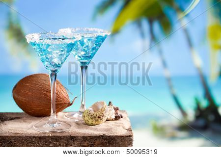 Fresh cocktail with blue curacao on beach background