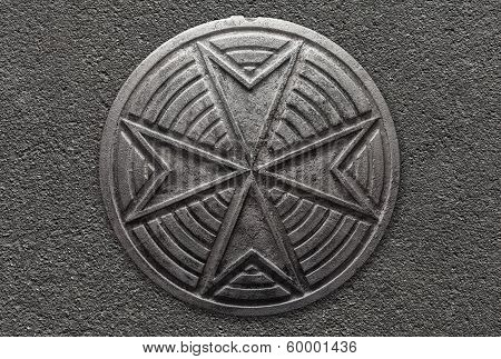 Round Vintage Sewer Manhole With Cross Pattern On Asphalt