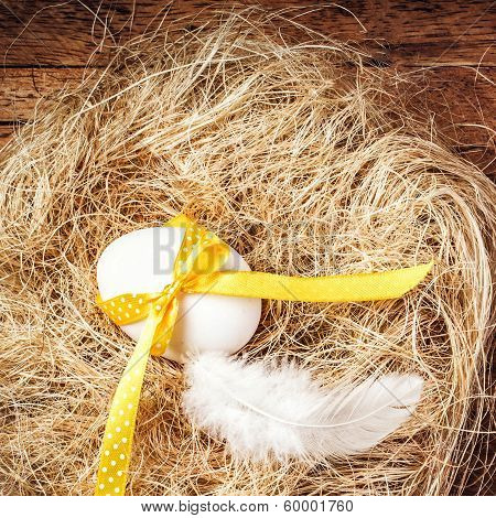 Easter Nest With Egg, Yellow Ribbon And White Feather On Wooden Background With Copyspace For Text