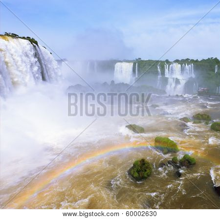 White whipped foam of water and a thin mist over the water. Magnificent rainbow bent in mist. The most high-water waterfall in the world - Iguazu. The picture is taken by lens Fisheye