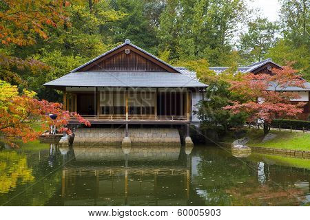 Tea House Reflecting In Pond In Japanese Garden