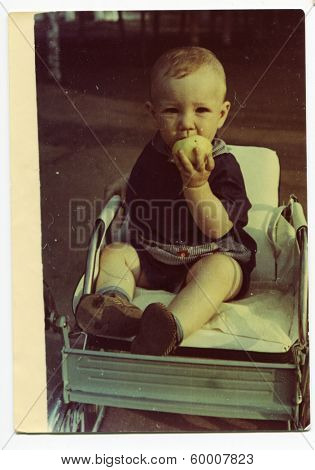 KURSK, USSR - CIRCA 1970: An antique photo shows portrait of a little boy eating an Apple sitting in a wheelchair.