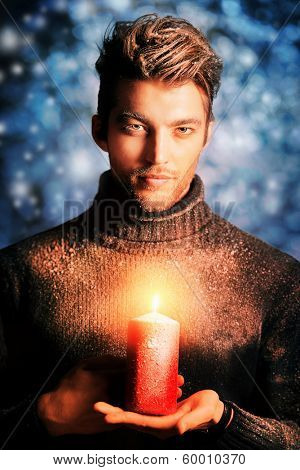 Portrait of a handsome man dressed in winter clothes and holding a candle, covered with snow.
