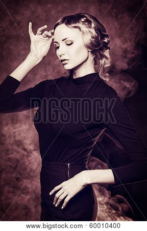 Elegant young woman in black clothes posing at studio.
