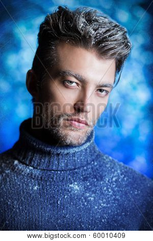 Portrait of a handsome man dressed in winter clothes, covered with frost and snow.