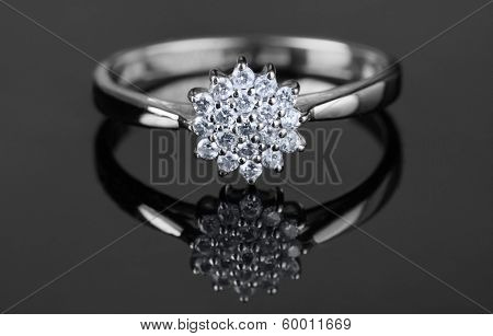 White gold ring with diamonds shot on grey surface, macro