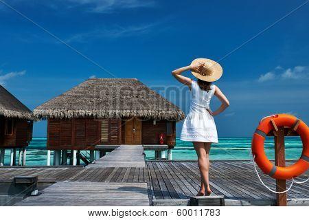 Woman on a tropical beach jetty at Maldives