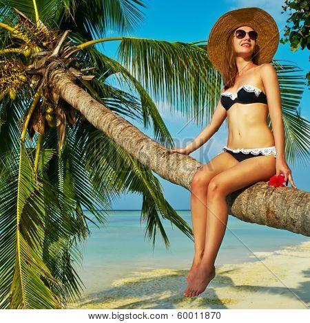 Woman in bikini sitting on a palm tree at tropical beach, Maldives