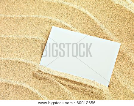 Empty white card is lying on a sea sand summer sunny background