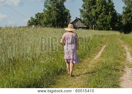 Walking woman in a straw hat among a field of rye