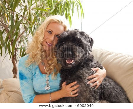 Young blond woman on a couch with her dog