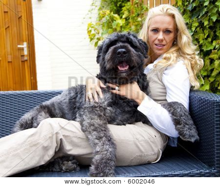 Young woman on a garden couch with a dog