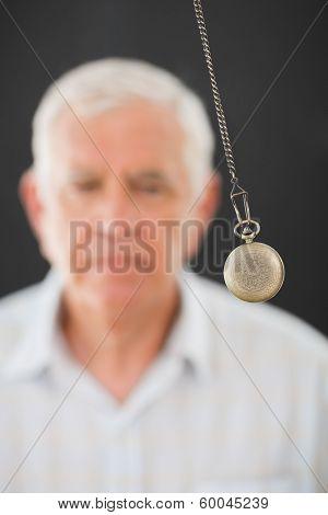 Senior man being hypnotized with pendulum over black background