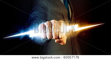 Businessman holding lightning in fist. Power and control