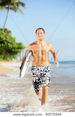 Beach lifestyle people - man surfer with surfing bodyboard running in water on tropical beach. Fit male fitness model having summer vacation holidays fun on Kaanapali beach, Maui, Hawaii, USA.