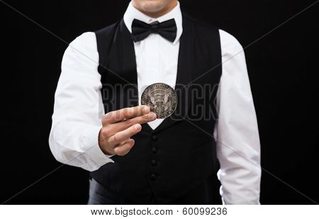 magic, performance, circus, casino and show concept - casino dealer holding half dollar coin