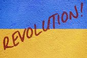 Ukraine flag graffiti painted on old concrete coated wall with REVOLUTION catchword inscription poster