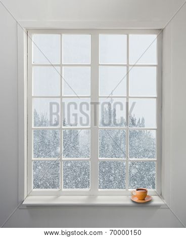 Modern residential window with a cup of tea and snowstorm on the background