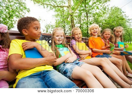 Happy school kids on bench sit in row together
