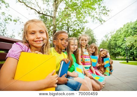 Kids sitting together on brown bench with books