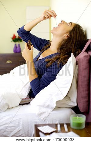 Sick Woman Taking Medicine In Bed