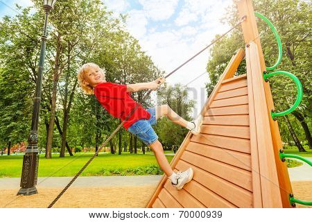 Positive boy climbs on wooden construction