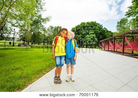 Two friends stand close to each other in park