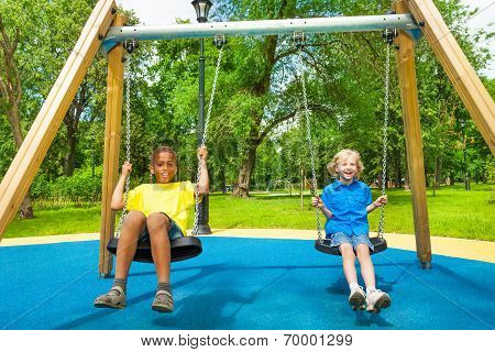 Two boys swing together and hold chains of swings
