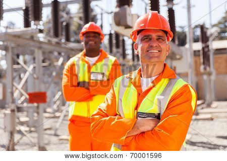 handsome middle aged electrical worker looking up with colleague on background