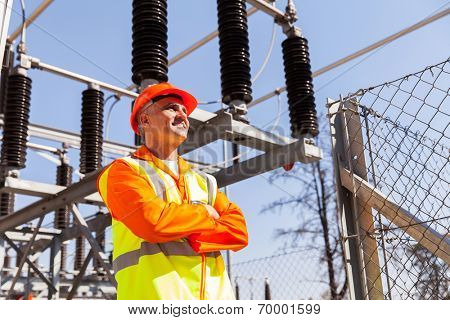 senior power plant technician with arms crossed in substation