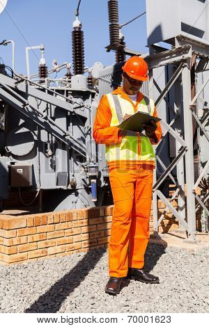 african power company technical worker writing on clipboard in power plant