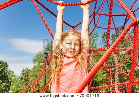 Happy girl hanging on red rope of net outside