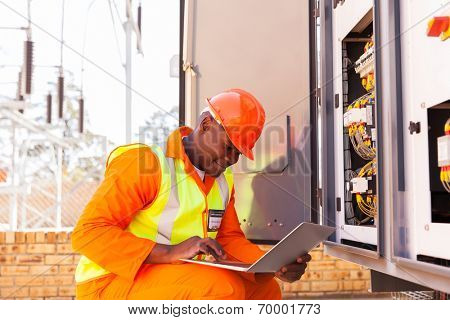 handsome african electrical engineer working on laptop next to transformer