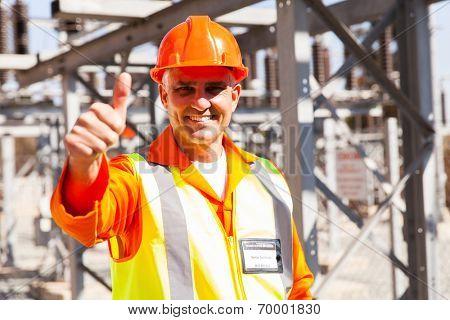 happy senior power company technician giving thumb up in substation