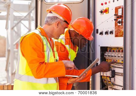 two experienced industrial technicians checking transformer
