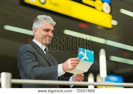 smiling senior businessman looking at his air ticket at airport