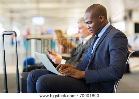 young african american businessman using laptop while waiting for his flight