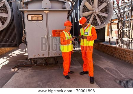 two electrical engineers working together in front of transformer