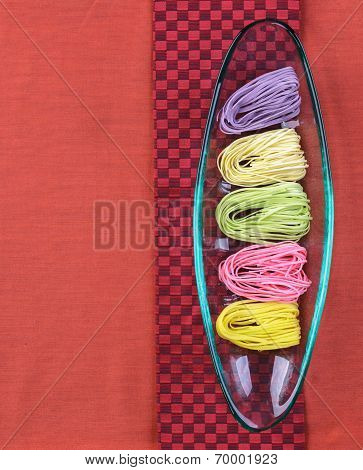 Colorful dried noodles in glass tray