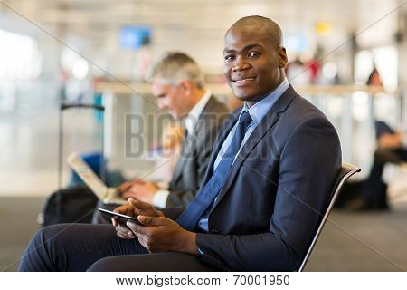 handsome african business traveler using tablet pc at airport