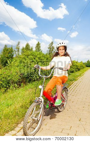 Pretty girl in bicycle helmet rides a bike